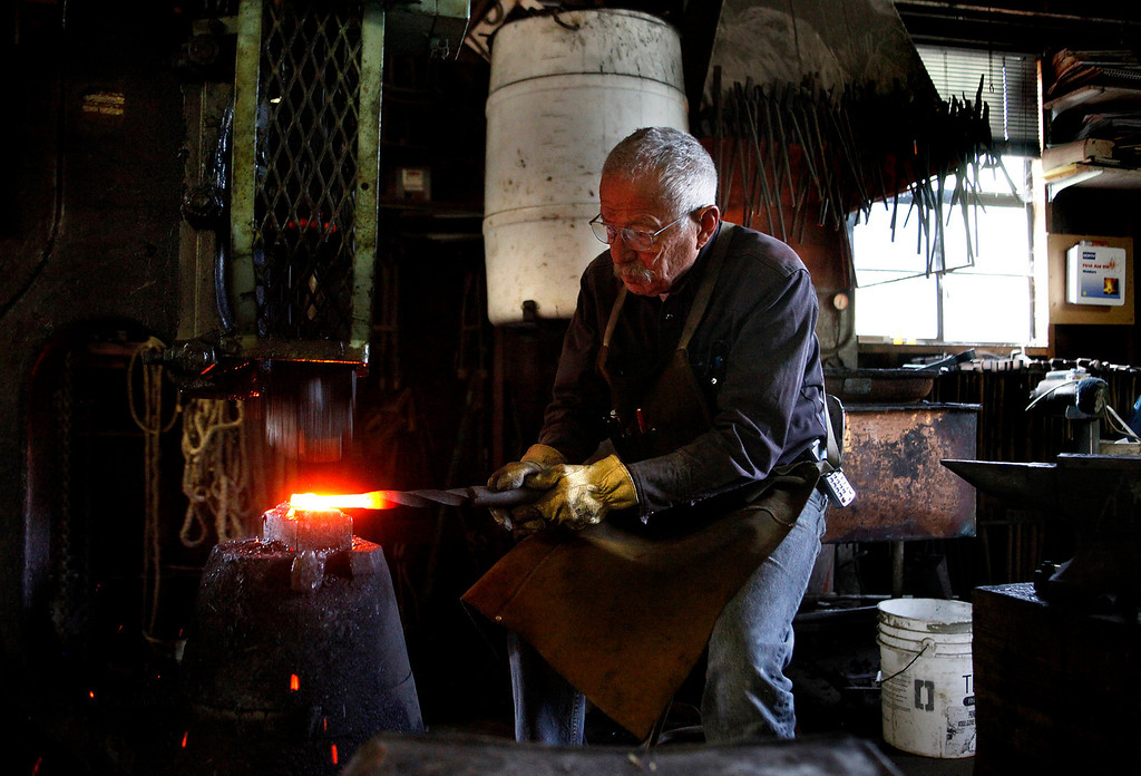 Description of . Blacksmith John Hudson, 78, uses a forging hammer at his shop across from Point Lobos in Carmel, Calif. on Wednesday August 21, 2013.  (Photo David Royal/ Monterey County Herald)