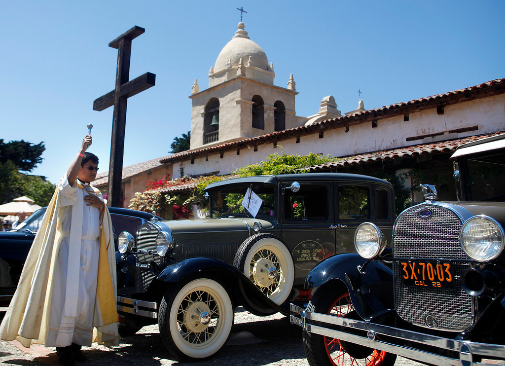 Description of . Father Fredy Calvario blesses a 1931 Ford Model A, center, and a 1929 Ford Model A during the Blessing of the Cars at Carmel Mission in Carmel, Calif. on Wednesday August 14, 2013. The 1931 is owned by Richard Atwell and participated in the Paris to London Road Race. The 1929 is owned by Richard Ring.  (Photo David Royal/ Monterey County Herald)