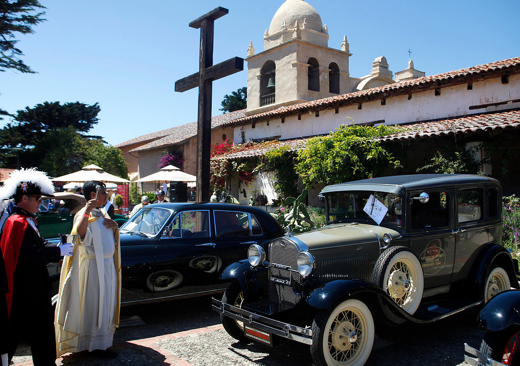 Description of . Father Fredy Calvario blesses a 1931 Ford Model A, center, during the Blessing of the Cars at Carmel Mission in Carmel, Calif. on Wednesday August 14, 2013. At far left is Knights of Columbus member Christian Theroux. The 1931 is owned by Richard Atwell and participated in the Paris to London Road Race.  (Photo David Royal/ Monterey County Herald)