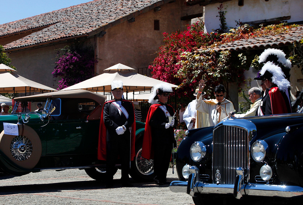Description of . Father Fredy Calvario is surrounded by Knights of Columbus as he says a prayer during the Blessing of the Cars at Carmel Mission in Carmel, Calif. on Wednesday August 14, 2013. At left is a 1929 Packard owned by Pat Phinny, at right is a 1951 Bentley Continental owned by Richard Atwell. The  Bentley was perviously owned by actor Cary Grant.   (Photo David Royal/ Monterey County Herald)