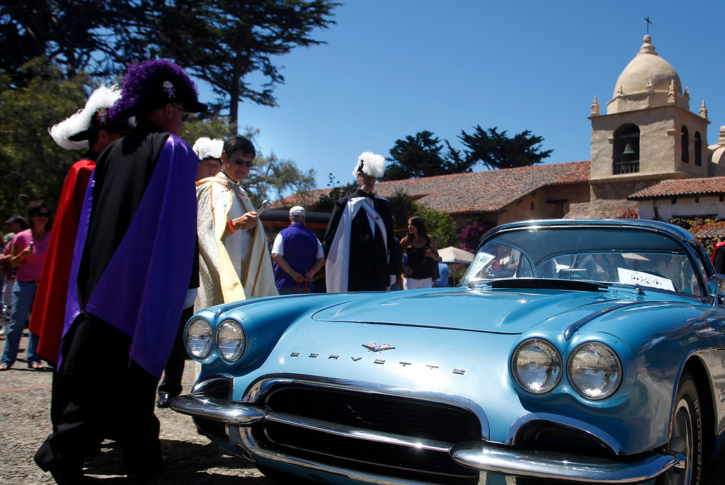 Description of . Father Fredy Calvario blesses a 1961 Chevrolet Corvette owned by david Hutchings during the Blessing of the Cars at Carmel Mission in Carmel, Calif. on Wednesday August 14, 2013.  (Photo David Royal/ Monterey County Herald)