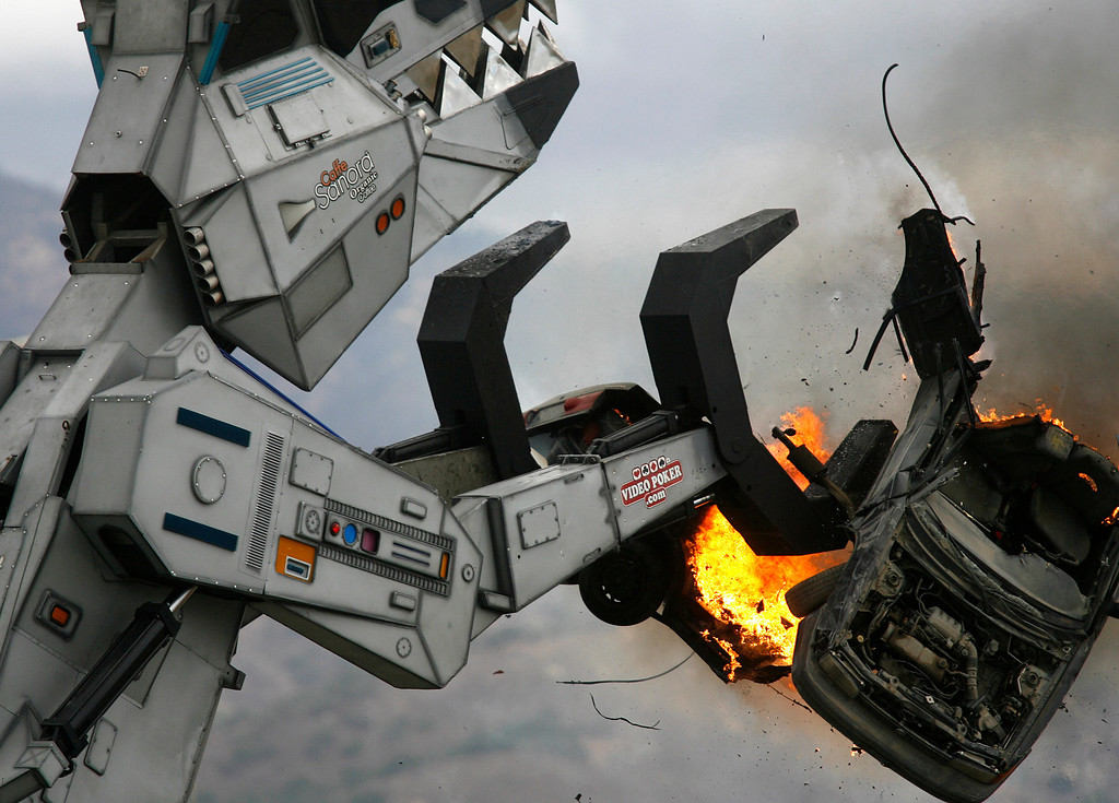 Description of . Robosaurus rips a car in half during the California International Airshow Salinas at the Salinas Airport in Salinas, Calif. on Saturday September 21, 2013.  (Photo David Royal/ Monterey County Herald)