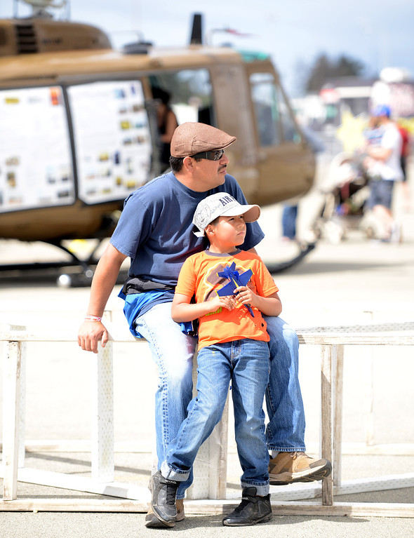 Description of . A father and his son watch planes fly overhead during the California International Airshow Salinas at the Salinas Airport in Salinas, Calif. on Saturday September 21, 2013.  (Photo David Royal/ Monterey County Herald)