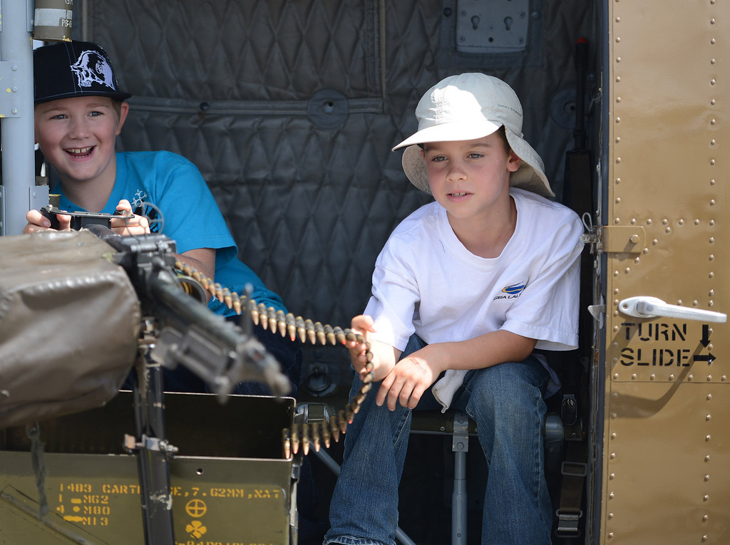 Description of . Cole Brewer and his friend Quentin Williams, both 8, of Prunedale play with a M-60 Machine Gun inside a Huey EMU 309 helicopter during the California International Airshow Salinas at the Salinas Airport in Salinas, Calif. on Saturday September 21, 2013. The restored helicopter first flew in Vietnam in 1965 and serves as an active tribute to those who served as part of Hueyvets.com. (Photo David Royal/ Monterey County Herald)