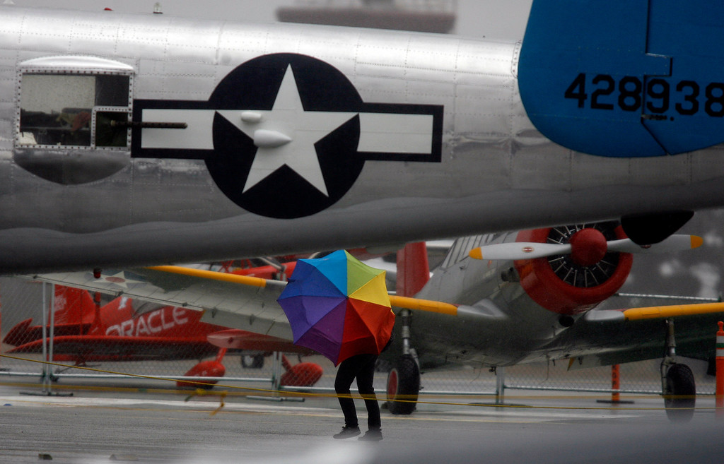 Description of . A person with an umbrella seeks shelter behind the tail of a B-25 Mitchell as rain falls on the California International Airshow Salinas at the Salinas Airport in Salinas, Calif. on Saturday September 21, 2013.  (Photo David Royal/ Monterey County Herald)