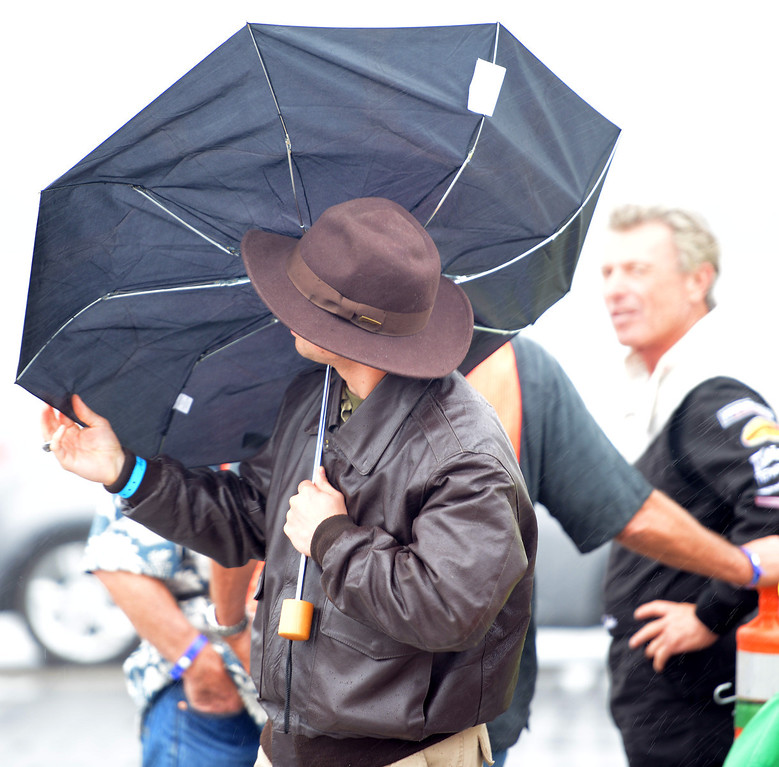 Description of . Richard Berghoff tries to salvage his umbrella as stunt pilot Shawn D. Tucker, right, waits for the rain to pass so he can fly during the California International Airshow Salinas at the Salinas Airport in Salinas, Calif. on Saturday September 21, 2013.  (Photo David Royal/ Monterey County Herald)