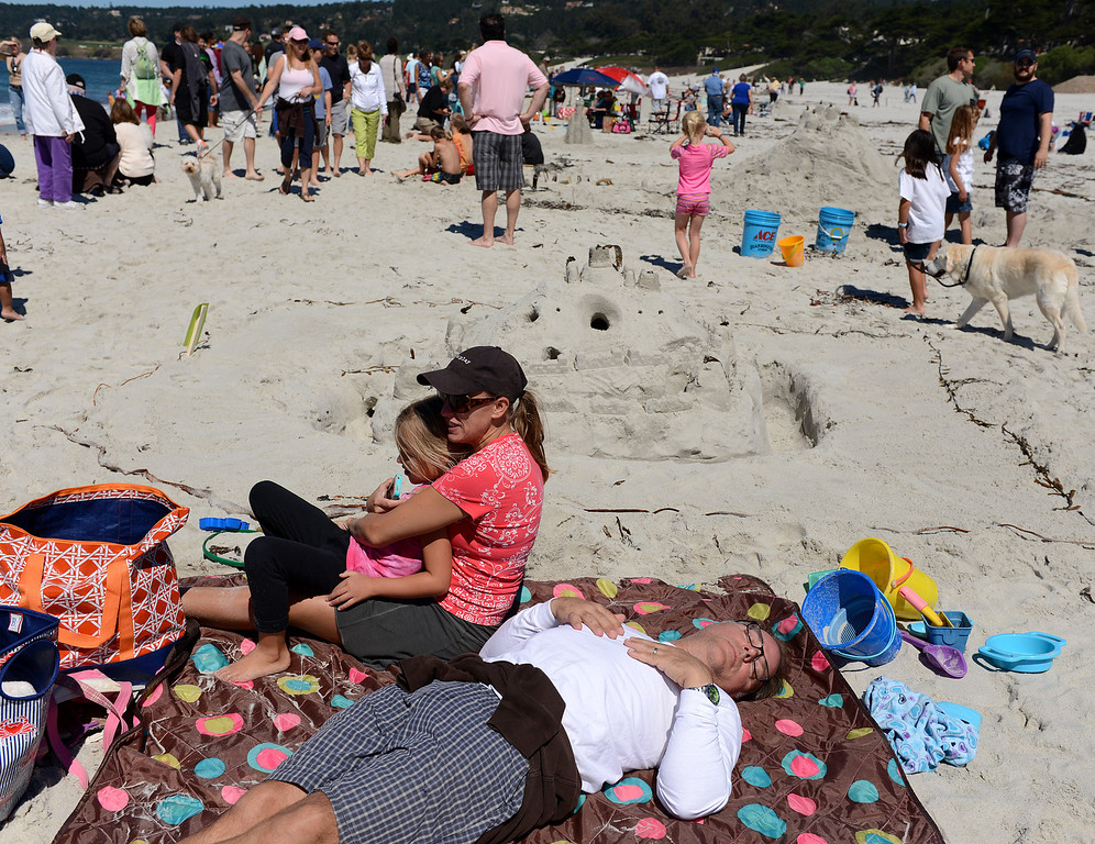 Description of . Tucker Bunch, of Carmel Valley, naps beside his wife Victoria and daughter Kate, 7, after building a castle with his family during the Sand Castle Contest on Carmel Beach in Carmel, Calif. on Sunday September 15, 2013. (Photo David Royal/ Monterey County Herald)