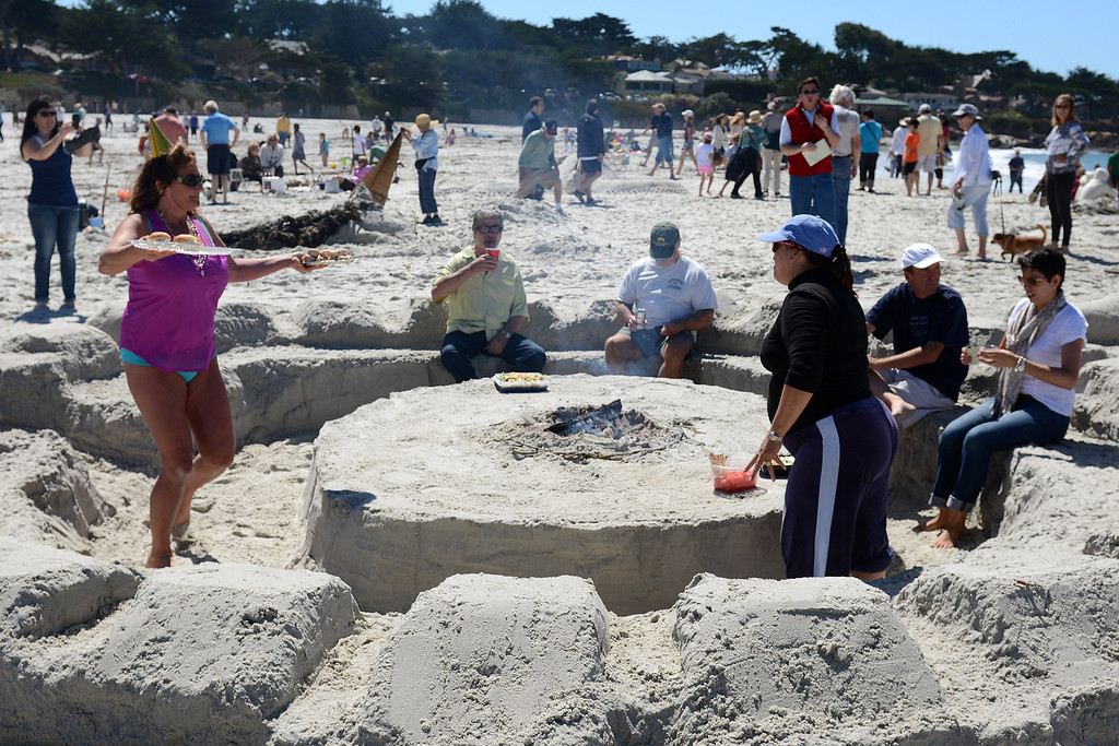Description of . A group of friends from Carmel eat lunch in a seating area castle they dug from the sand during the Sand Castle Contest on Carmel Beach in Carmel, Calif. on Sunday September 15, 2013. (Photo David Royal/ Monterey County Herald)