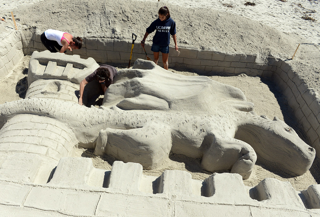 Description of . Pilar Batillo, center, of Palo Alto gets help her niece Melissa Crane, right, and friend Andrea Clerici putting the finishing touches on their dragon castle during the Sand Castle Contest on Carmel Beach in Carmel, Calif. on Sunday September 15, 2013. This years theme was Once Upon a Castle. (Photo David Royal/ Monterey County Herald)