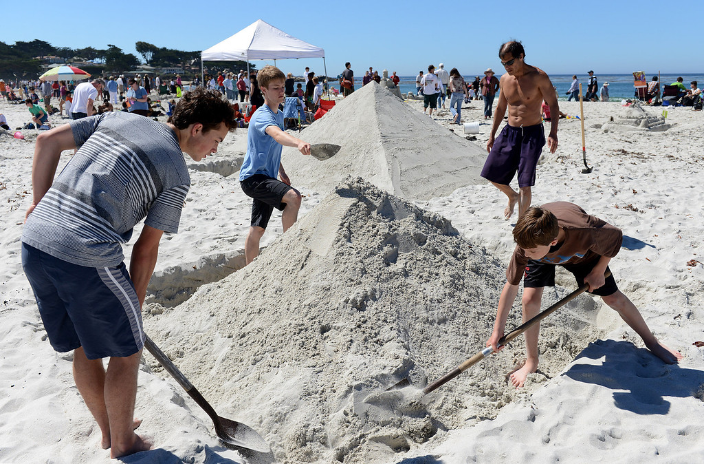 Description of . Eugene Loh, clockwise from center right, of Pacific Grove works on a sand castle version of the Great Pyramids of Giza with sons Henry, 13, Jacob, 17 and friend Eric O'Hagan during the Sand Castle Contest on Carmel Beach in Carmel, Calif. on Sunday September 15, 2013. (Photo David Royal/ Monterey County Herald)