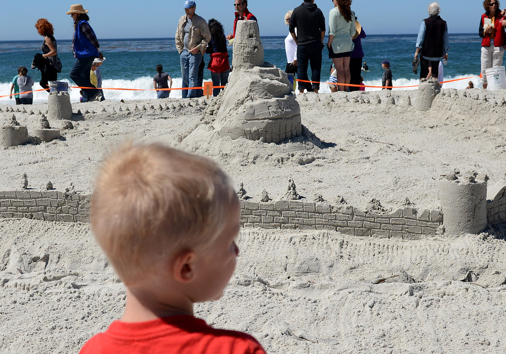 Description of . A boy looks over the castle built by Carmel River School students during the Sand Castle Contest on Carmel Beach in Carmel, Calif. on Sunday September 15, 2013. (Photo David Royal/ Monterey County Herald)