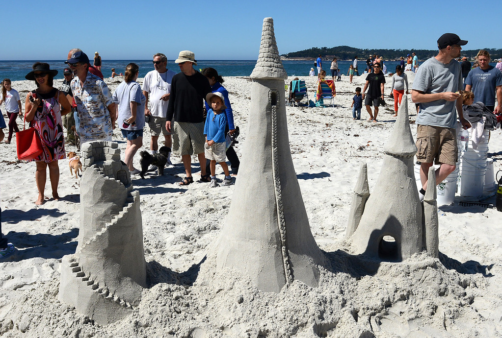 Description of . Scott Weaver, right, eats a snack, while waiting for judges to arrive after building Sleeping Beauty's Tower, left, Rapunzel's Tower and Cinderella's Tower during the Sand Castle Contest on Carmel Beach in Carmel, Calif. on Sunday September 15, 2013. Rapunzel's Tower featured sand hair hanging out of the window. (Photo David Royal/ Monterey County Herald)