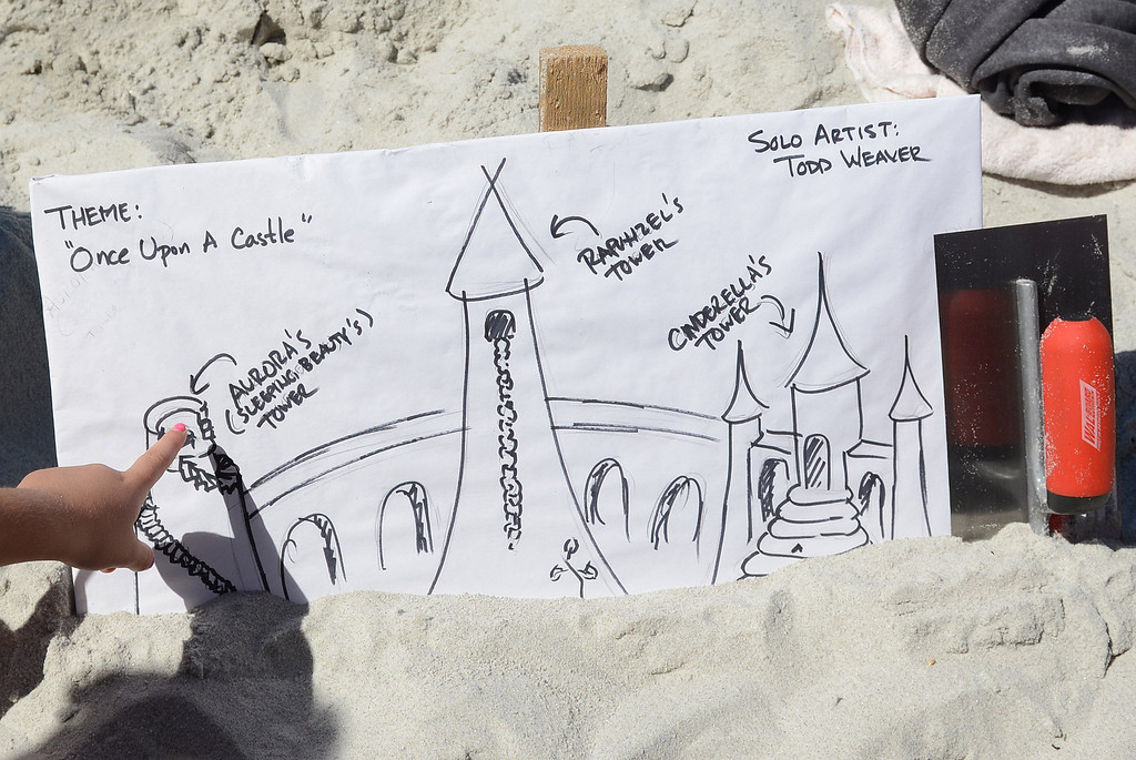 Description of . A young fan looks at Scott Weaver's sketch of Sleeping Beauty's Tower, left, Rapunzel's Tower and Cinderella's Tower during the Sand Castle Contest on Carmel Beach in Carmel, Calif. on Sunday September 15, 2013. (Photo David Royal/ Monterey County Herald)
