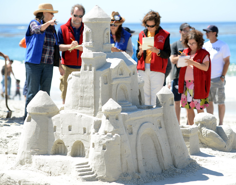 Description of . Sand Castle Contest judges take a close look at the Storybook Dreams which had a castle rising out of a book that a child was reading at Carmel Beach in Carmel, Calif. on Sunday September 15, 2013. The castle, built by the Mehringer Family of Monterey, won the Golden Shovel Award. (Photo David Royal/ Monterey County Herald)