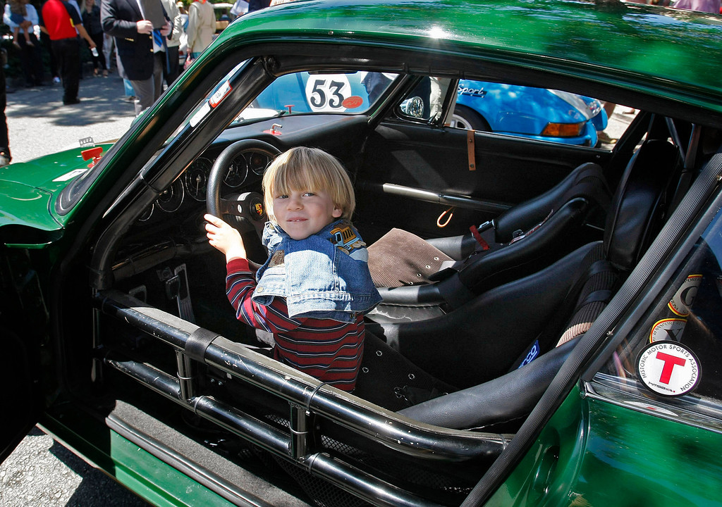 Description of . James Luc-Pierre Gagnon, 4, from Sacramento gets a thrill by being able to sit in George Calfo's 1967 Porsche 911S at the Concours on the Avenue in Carmel on Agust 13, 2013.  (Vern Fisher/Monterey County Herald)
