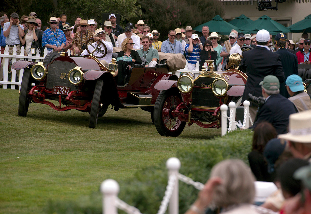 Description of . Spectators cover their ears as two early 1900's Simplex automobiles backfire at the 2013 Concours d'Elegance. (Matthew Hintz/Monterey County Herald)