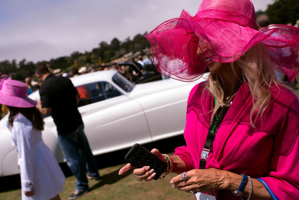 Description of . Daru Kawalkowski, dressed in hot pink, meanders her way through the automobiles parked on the 18th fairway at Pebble Beach golf course Sunday, August 18th, 2013 during the 2013 Concours d'Elegance. (Matthew Hintz/Monterey County Herald)