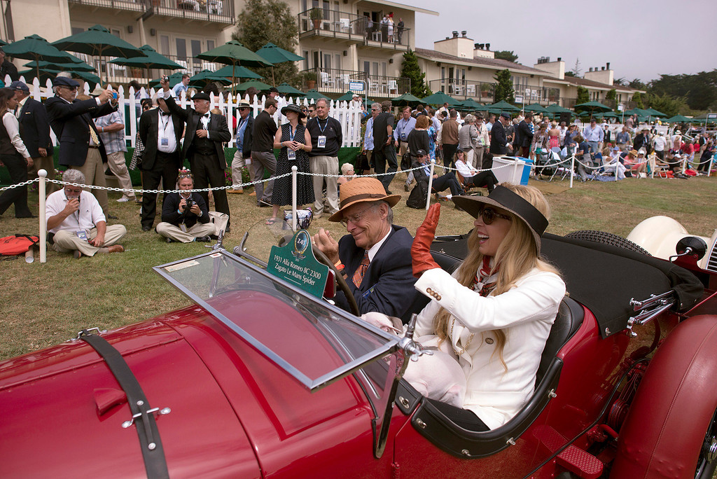Description of . Rob and Melani Walton wave to spectators as they cue up in front of the Concours d'Elegance stage Sunday, August 18th, 2013 in in their 1931 Alfa Romeo 8C 2300 Le Mans Spider. (Matthew Hintz/Monterey County Herald)