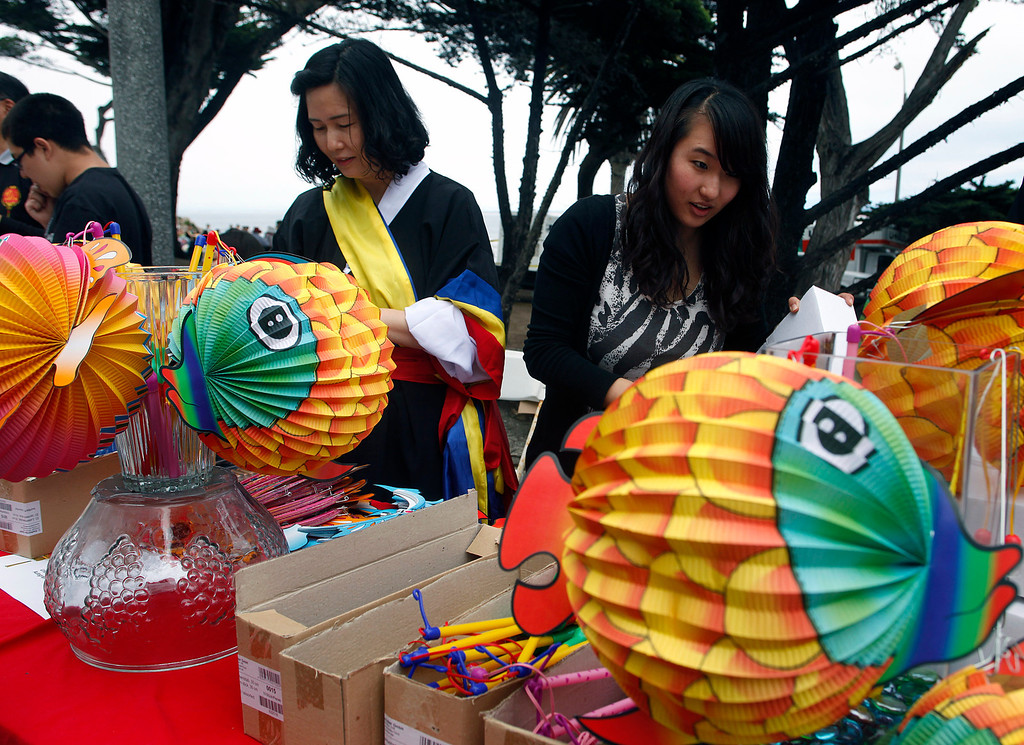 Description of . Sonhee Cho, right and her mother Meesun Cho prepares a lighted lantern for sale while volunteering during Feast of Lanterns festivities at Lovers Point Pacific Grove, Calif. on Saturday July 26, 2013.  (Photo David Royal/ Monterey County Herald)