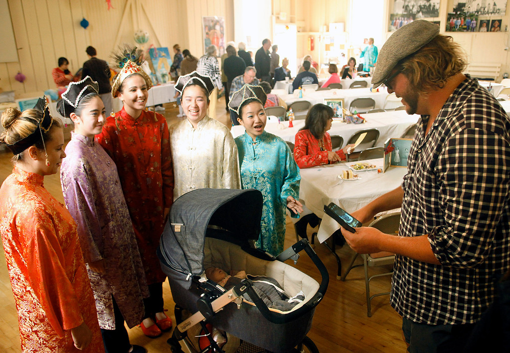 Description of . Courtney Lyon, center left in red, Queen of the Feast of Lanterns and her Royal Court composed of Caroline Gruber, left, Hayley Yukihiro, Ashley Yukihiro and Minhee Cho pose with Vivienne Bowlus, one month, as her father Garrett Bowlus shoots a photo during the Feast Of Flavors lunch at Chautauqua Hall in Pacific Grove, Calif. on Thursday July 25, 2013. The lunch showcases dishes donated by local restaurants with proceeds going to scholarships for the members of the Royal Court. (Photo David Royal/ Monterey County Herald)