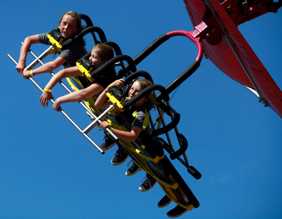 Description of . Jake Haney, 12, left, his brother Gavin, 9, right, and their cousin Gabi DaSilva, 12, all of Pacific Grove ride the Cliff Hanger ride at the Monterey County Fair in Monterey, Calif. on Sunday September 1, 2013.  (Photo David Royal/ Monterey County Herald)