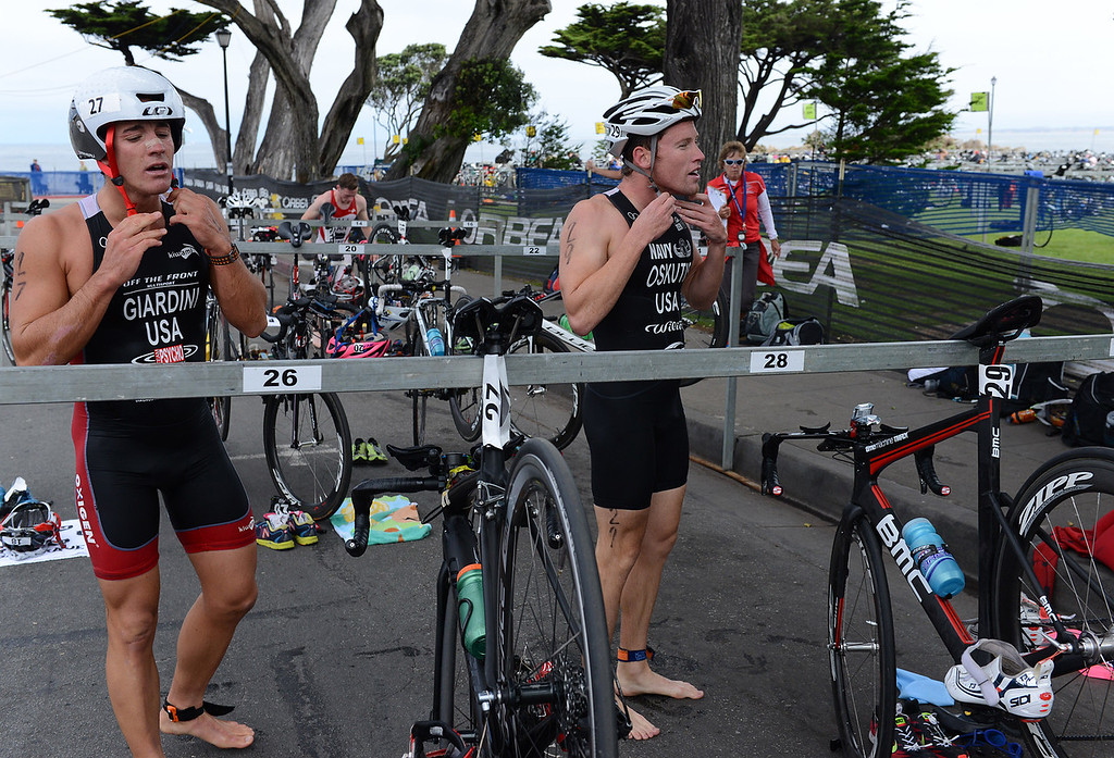 Description of . Davide Gardini and Derek Oskutis transition from the swim ti their bicycles during the Elite Race at the Pacific Grove Triathlon in Pacific Grove, Calif. on Saturday September 14, 2013.  Photo David Royal/ Monterey County Herald)