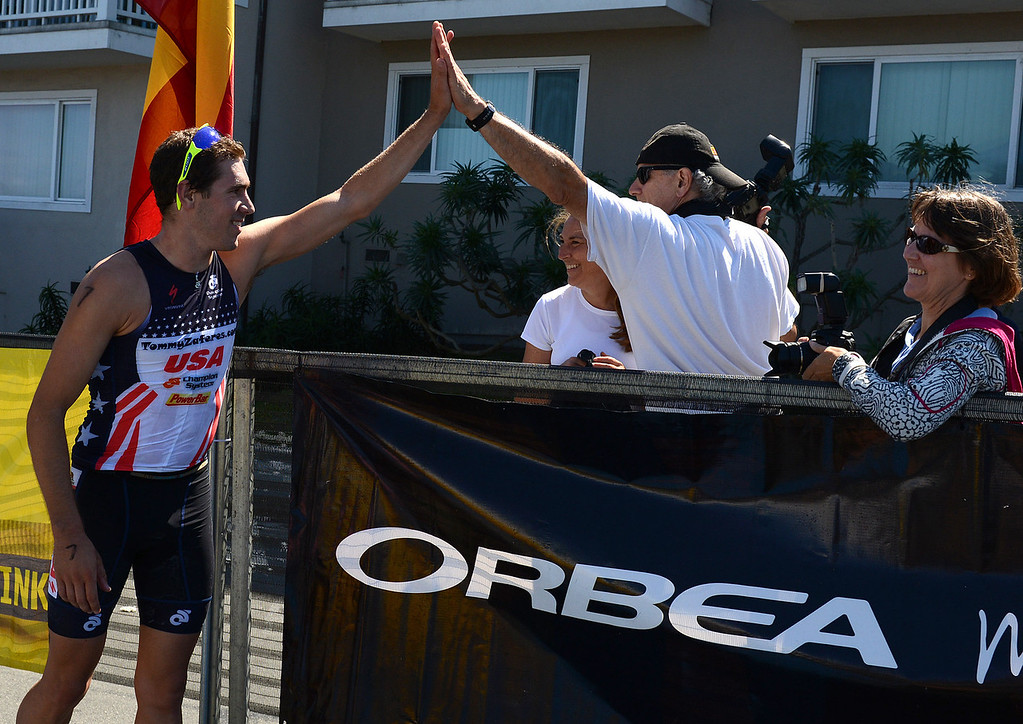 Description of . Mens winner Tommy Zaferes of Aptos, Calif. greets his father George after winning the Elite Race at the Pacific Grove Triathlon in Pacific Grove, Calif. on Saturday September 14, 2013.  Photo David Royal/ Monterey County Herald)