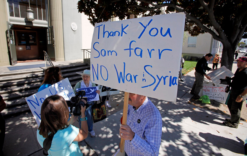 Description of . Gary Karnes (holding sign) with the Peace Coalition of Monterey County in a demonstration in Salinas on September 4, 2013 against possible US military action in Syria.  (Vern Fisher/Monterey County Herald)