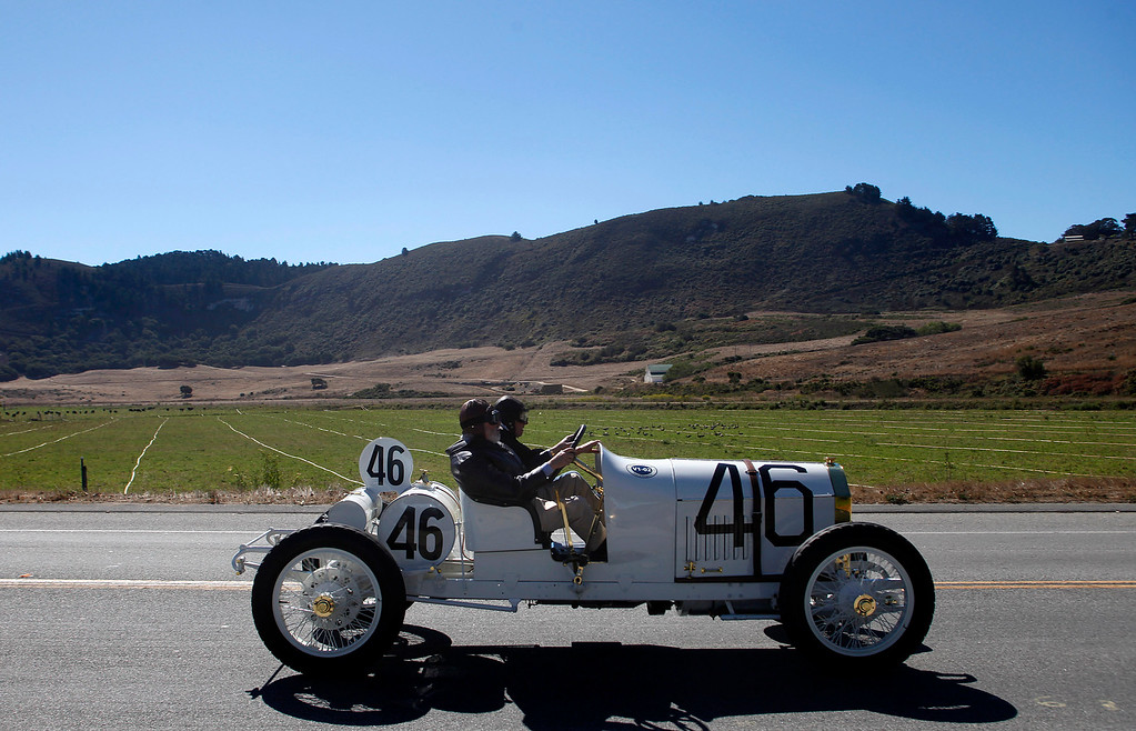 Description of . A 1908 Benz 105 HP Prinz Heinrich Two Seat Race car owned by Bruce and Jolene McCaw drives past the old Odello Ranch on their way south toward Big Sur on Highway 1 during Pebble Beach Tour d'Elegance in Carmel, Calif. on Thursday August 15, 2013. The Route starts in Pebble Beach, passes through Laguna Seca Raceway, Carmel Valley and Big Sur before returning to the Monterey Peninsula.  (Photo David Royal/ Monterey County Herald)