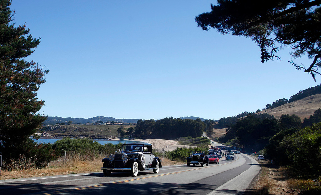 Description of . A 1930 Cadillac 452 Fleetwood Coupe owned by Rudy Langer leads a line of classic cars past Monastery Beach on their way south toward Big Sur on Highway 1 during Pebble Beach Tour d'Elegance in Carmel, Calif. on Thursday August 15, 2013. The Route starts in Pebble Beach, passes through Laguna Seca Raceway, Carmel Valley and Big Sur before returning to the Monterey Peninsula.  (Photo David Royal/ Monterey County Herald)