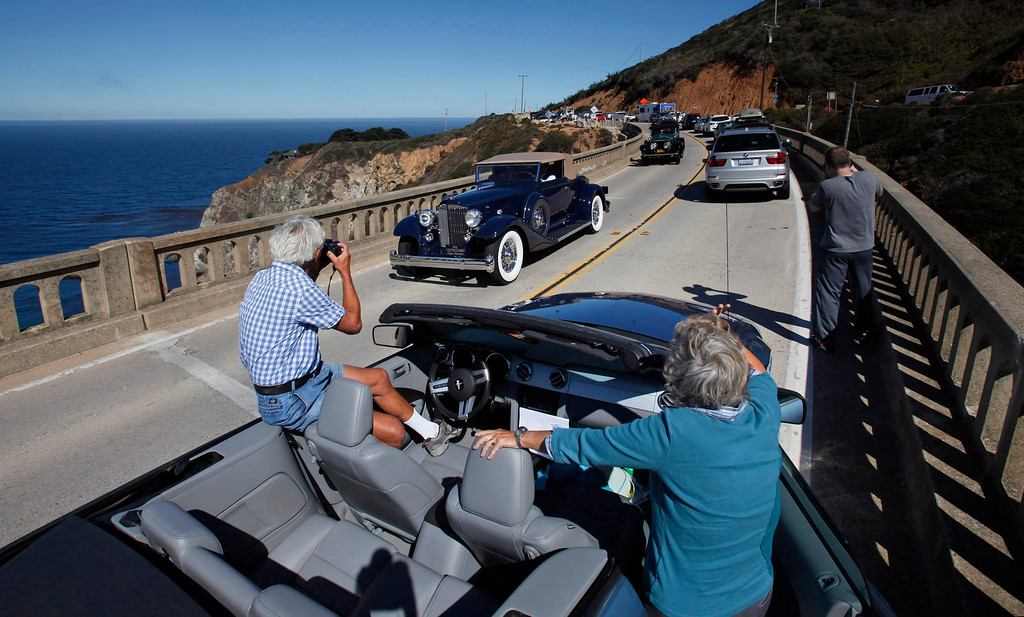 Description of . Mike and Myrna Sonstein from Oceanside stop to photograph passing classic cars on  Highway 1 over the Bixby Creek Bridge during the Tour d'Elegance on August 15, 2013.  (Vern Fisher/Monterey County Herald)