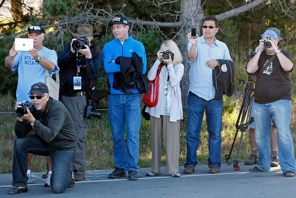 Description of . Spectators line up in Pebble Beach to photograph passing classic cars during the Tour d'Elegance on August 15, 2013.  (Vern Fisher/Monterey County Herald)
