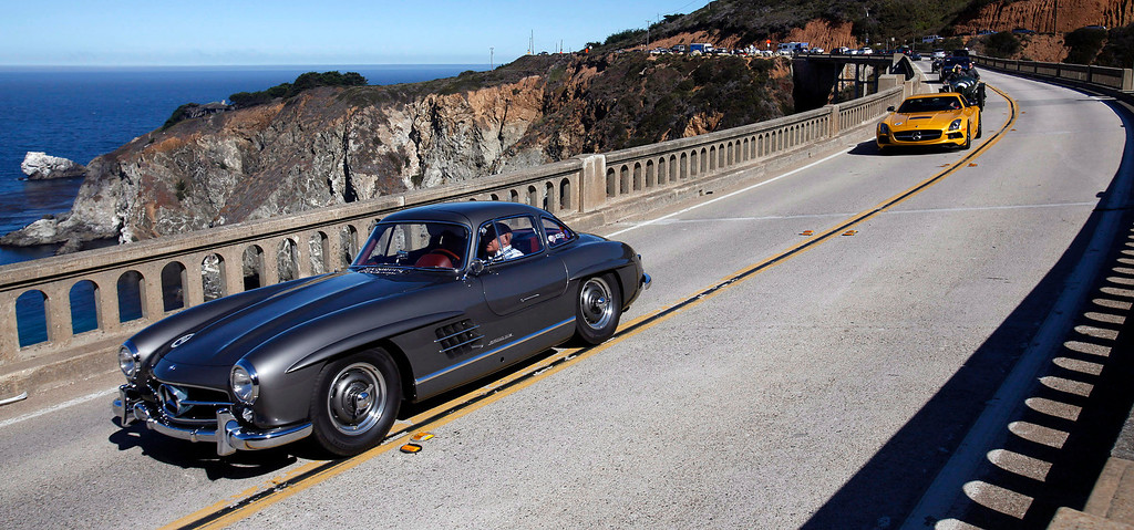 Description of . Sir Stirling Moss leads a group of classic cars south on Highway 1 over the Bixby Creek Bridge during the Tour d'Elegance on August 15, 2013.  (Vern Fisher/Monterey County Herald)