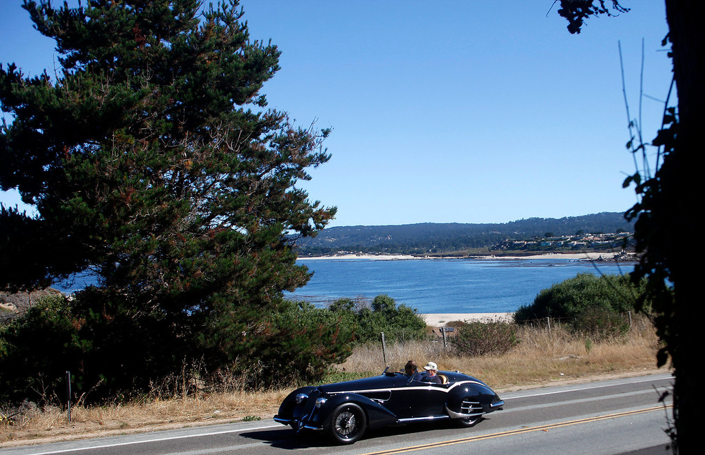 Description of . A classic car rolls past Monastery Beach on it's way south toward Big Sur on Highway 1 during Pebble Beach Tour d'Elegance in Carmel, Calif. on Thursday August 15, 2013. The Route starts in Pebble Beach, passes through Laguna Seca Raceway, Carmel Valley and Big Sur before returning to the Monterey Peninsula.  (Photo David Royal/ Monterey County Herald)