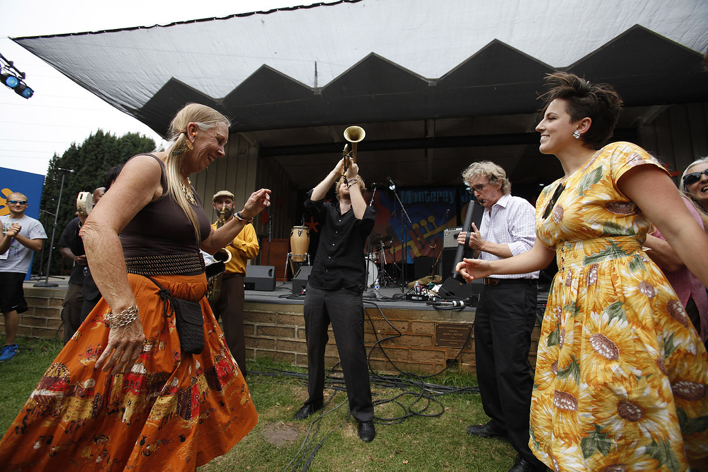 Description of . Barbara Alaimo and Briggette Barnato dance to the tunes of the California Honeydrops with front man Lech Wierzynski on trumpet during their performance on the Garden Stage at the Monterey Jazz Festival on Sept. 21, 2013.  (Vern Fisher/Monterey County Herald)