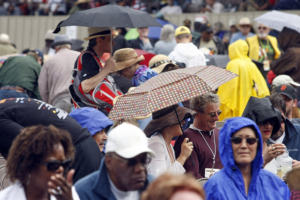 Description of . Umbrellas came out for a time at the main arena at the Monterey Jazz Festival on Sept. 21, 2013.  (Vern Fisher/Monterey County Herald)