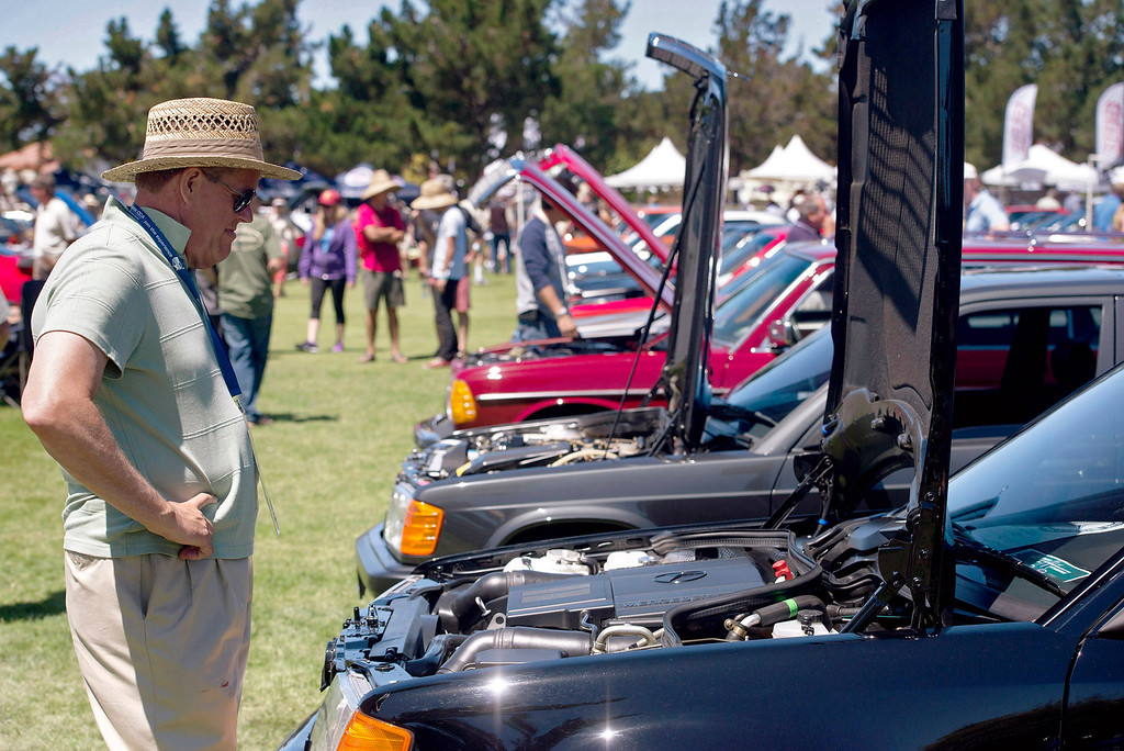 Description of . Jan Gullett inspects a line of Class 6 Mercedes Benzs during the Legends of the Autobahn car show at Rancho Canada Golf Course Friday, August 16th, 2013. (Matthew Hintz/Monterey County Herald)