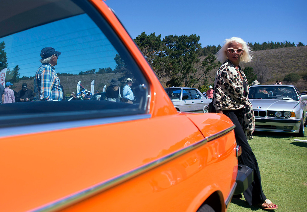 Description of . Marianne Leiven walks past Don Swiers 1974 2002 Tii BMW Friday, August 16th, 2013 at the Legends of the Autobahn car show at Rancho Canada Golf Course. (Matthew Hintz/Monterey County Herald)