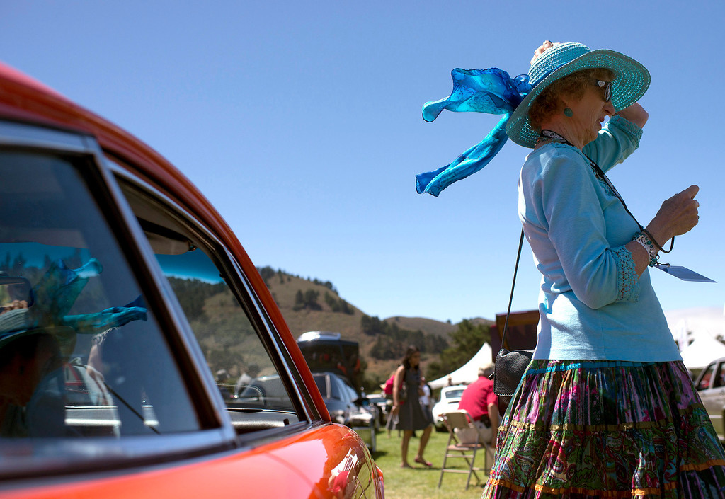 Description of . Emily Woollett's hat nearly comes off in a gust of wind, Friday, August 16th, at the Legends of the Autobahn car show at Rancho Canada Golf Course. (Matthew Hintz/Monterey County Herald)