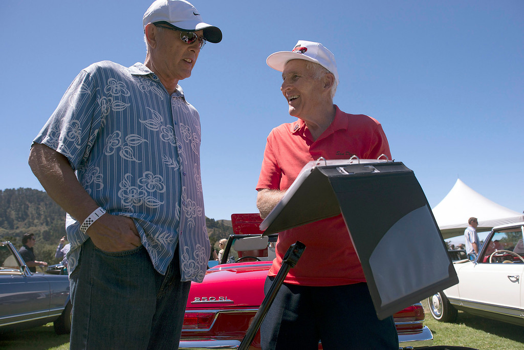 Description of . Byron Horter talks with owner, Gary Jarvis, about his red 1967 Mercedes Benz 250 SL, Friday, August 16th, 2013 during the Legends of the Autobahn car show at Rancho Canada Golf Course. (Matthew Hintz/Monterey County Herald)