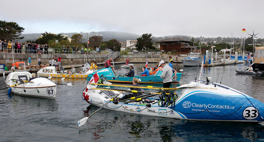 Description of . Rebecca Berger and Leanne Zrumtheir row their boat to the start line on June 9, 2014 in Monterey for the start of the Great Pacific Race 2014. Thirteen teams from around the world battle it out on a grueling 2,400 mile stretch of the Pacific Ocean from Monterey to Honolulu.  (Vern Fisher - Monterey Herald)