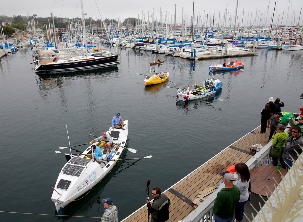 Description of . Entrants start to row out of the harbor in their boats on June 9, 2014 in Monterey for the start of the Great Pacific Race 2014. Thirteen teams from around the world battle it out on a grueling 2,400 mile stretch of the Pacific Ocean from Monterey to Honolulu.  (Vern Fisher - Monterey Herald)