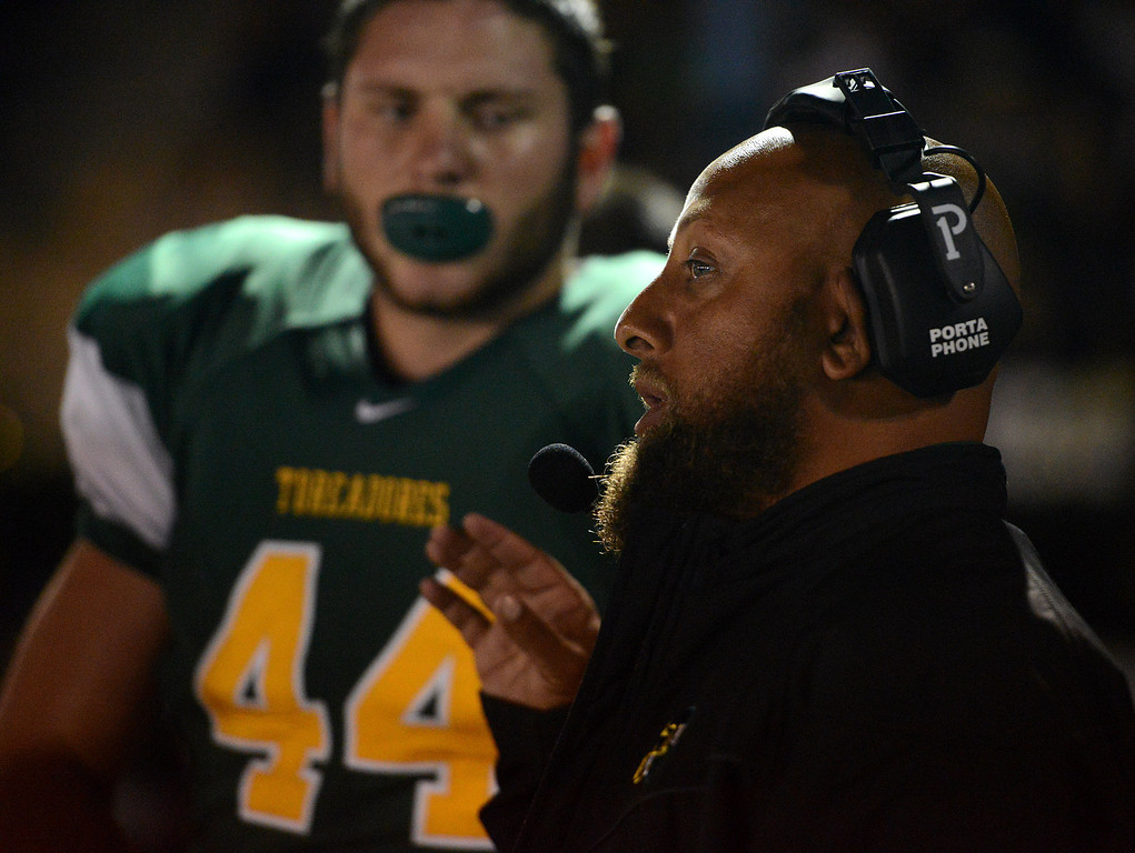 Description of . Monterey assistant coach Jimmy Hill speaks with player Joseph Pryor during football against Pacific Grove in Monterey, Calif. on Friday September 20, 2013.  (Photo David Royal/ Monterey County Herald)