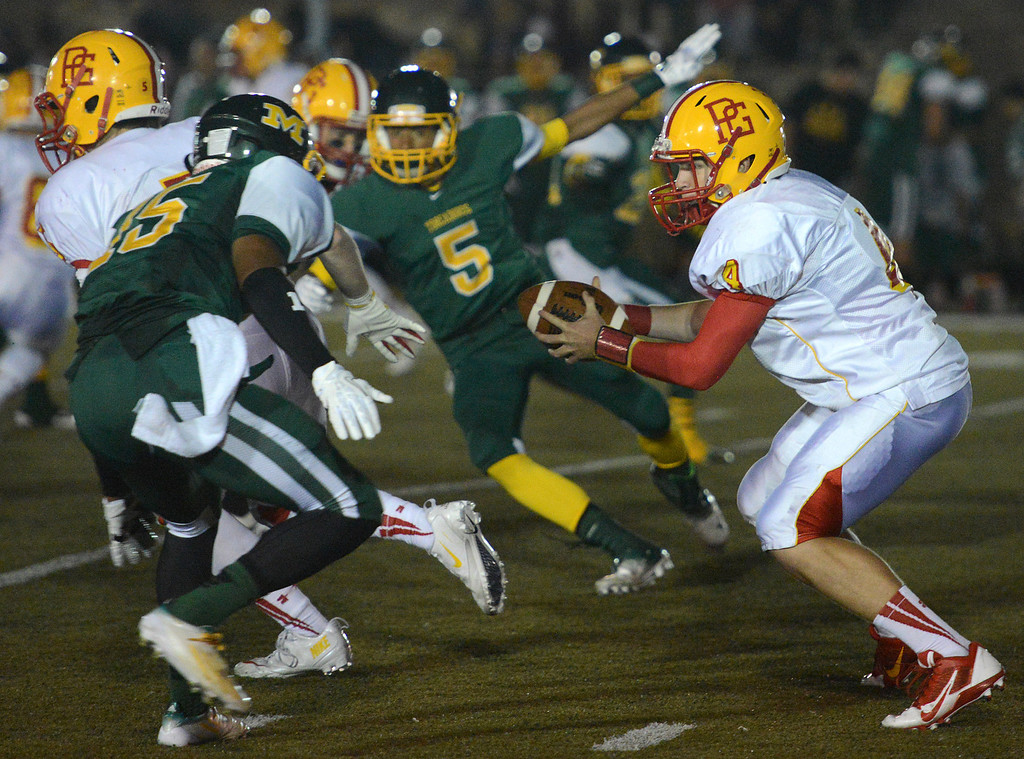 Description of . Pacific Grove's quarterback Luke Lowell works under pressure during football in Monterey, Calif. on Friday September 20, 2013.  (Photo David Royal/ Monterey County Herald)