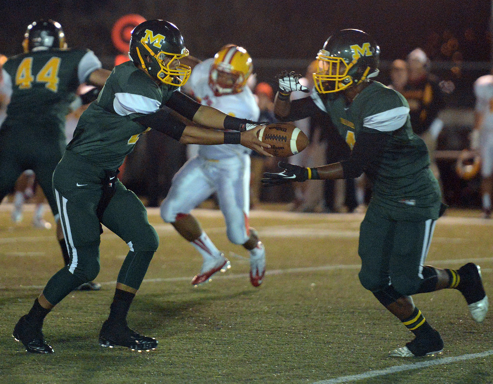 Description of . Monterey quarterback Carter Aldrete hands off to Akili Jones against Pacific Grove during football in Monterey, Calif. on Friday September 20, 2013.  (Photo David Royal/ Monterey County Herald)