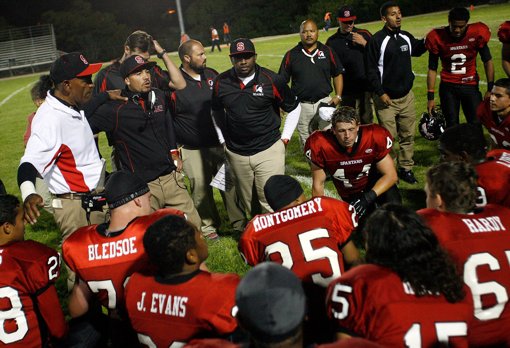Description of . Seaside coaches gather the team during half time against Skyline during football in Seaside, Calif. on Friday September 6, 2013. Photo David Royal/ Monterey County Herald)