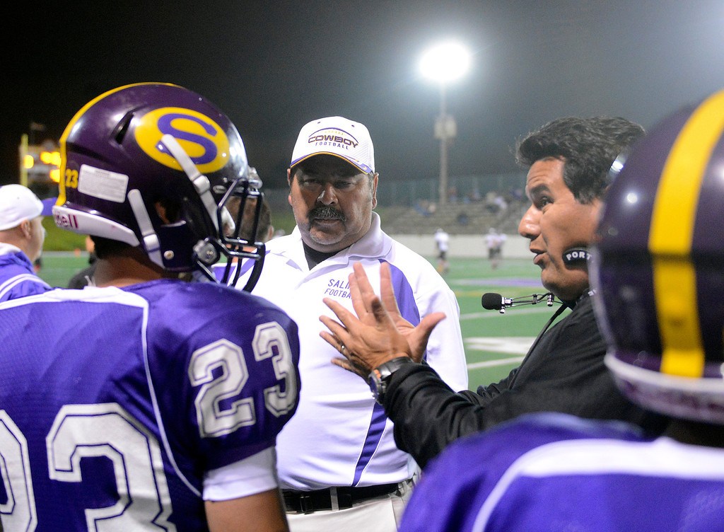 Description of . Salinas coaches speak with Vince LaSala during football against Seaside at Salinas on Friday October 18, 2013. (Photo David Royal/ Monterey County Herald)
