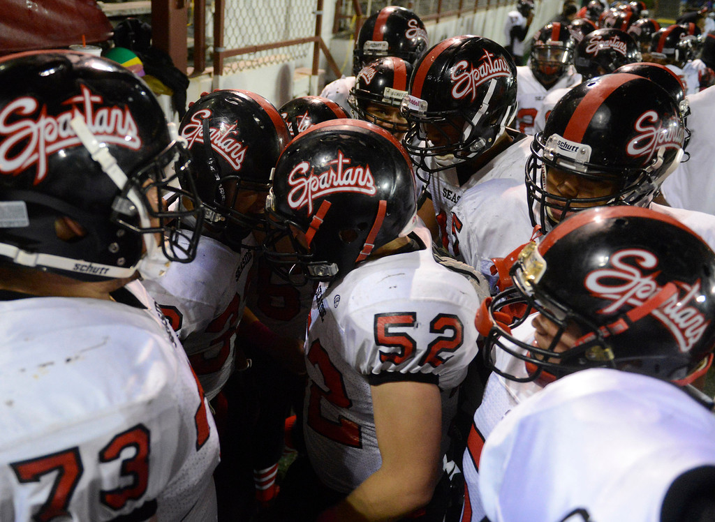 Description of . Seaside players gather around Fernando Avila, second from left, after he knocked the ball out of the hands of Salinas' Elijah Kirkland for a fumble during football at Salinas on Friday October 18, 2013. (Photo David Royal/ Monterey County Herald)
