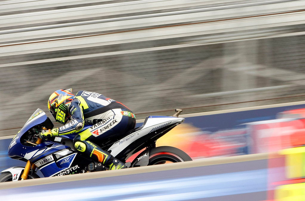 Description of . MotoGp rider Valentino Rossi from Italy races down the straight at Mazda Raceway Laguna Seca during the first day of practice on July 19, 2013.  (Vern Fisher/Monterey County Herald)