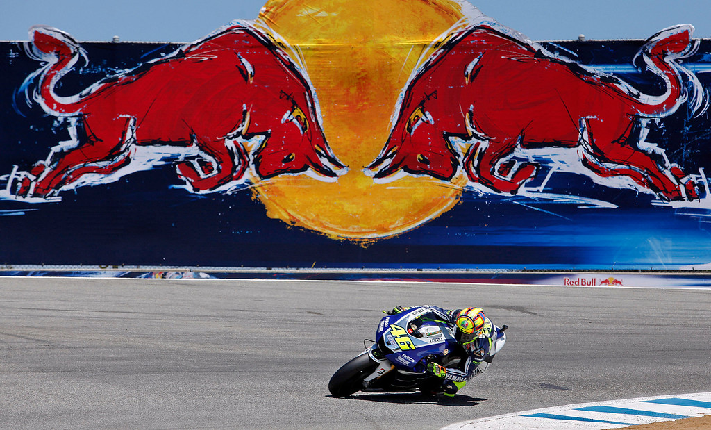 Description of . MotoGp rider Valentino Rossi from Italy heads in to the corkscrew at Mazda Raceway Laguna Seca during the first day of practice on July 19, 2013.  (Vern Fisher/Monterey County Herald)